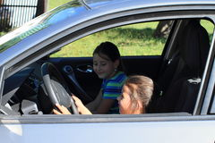 Girls driving a car. Smiling girl holding steering wheel and driving a silver car with opened window with her sister besides stock photography