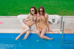 Girls drkinking cocktails on the pool Royalty Free Stock Photo