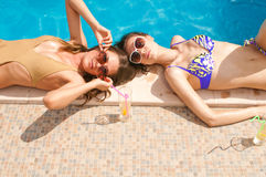 Girls drkinking cocktails on the pool Stock Image