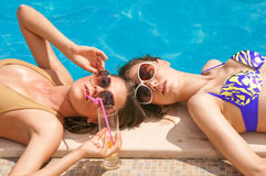 Girls drkinking cocktails on the pool Stock Photography