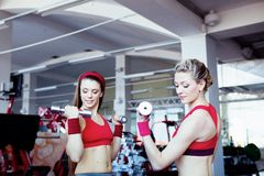 Girls with dumbbells in fitness center Stock Photos