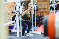 Girls in gym workout. Girls with dumbbells in gym workout in front of mirror Stock Image