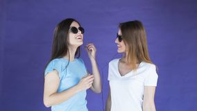 Girls in earphones dance. Two cheerful friends enjoying the music in earphones, wearing light blue and white t-shirts, dancing with great pleasure in the purple stock footage