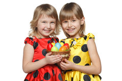 Girls with Easter eggs in a basket Stock Images