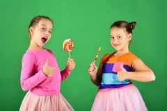 Girls eat big colorful sweet caramels. Children with happy faces. Pose with candies on green background. Sisters with round and long lollipops wink and show Royalty Free Stock Photos