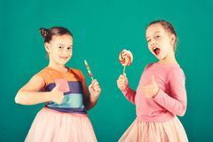 Girls eat big colorful sweet caramels. Children with happy faces. Pose with candies on green background. Sisters with round and long lollipops wink and show royalty free stock images