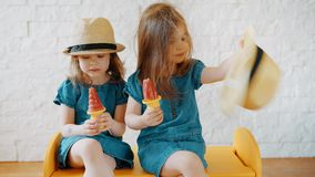 Girls eat ice cream at home while waiting for vacation. Two little girls eat ice cream at home while waiting for a summer vacation stock video footage