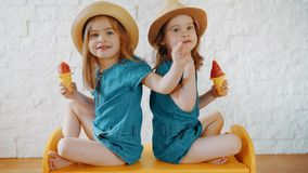 Girls eat ice cream, show something and wait for vacation. Two little girls eat ice cream, show something and wait for summer vacation stock video