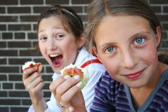 Girls eating apples Stock Images