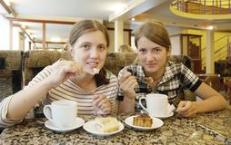 Girls  eating a biscuit pastry at coffee-room Stock Image