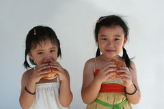 Girls eating burger. Two little girls holding and biting a hamburger Royalty Free Stock Photography