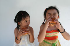 Girls eating burger. Two little girls holding and biting a hamburger Stock Photography