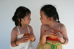 Girls eating burgers. Two little girls holding and biting a hamburger Royalty Free Stock Image