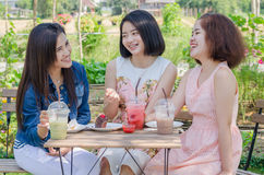 Girls eating cake and drink together at cafe Stock Photo