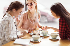 Girls eating cake and drinking coffee at cafe, coffee break Stock Photography