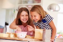 Girls Eating Ingredients Whilst Making Cheese On Toast Royalty Free Stock Image