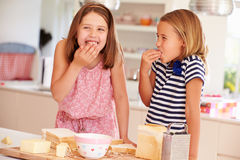 Girls Eating Ingredients Whilst Making Cheese On Toast Royalty Free Stock Photos