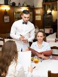 Girls eating out in restaurant. Young couple of girls eating out in a restaurant while handsome waiter is serving them Stock Photography