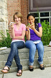 Girls eating pizza. Two teenage girls sitting and eating pizza Royalty Free Stock Photo