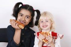 Girls eating pizza slice royalty free stock image