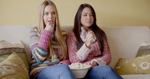 Girls Eating Popcorn While Watching Movie at Home. Two Pretty Girls in Winter Outfits Eating Popcorn Snacks While Watching a Movie Seriously at Home stock video