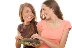 Girls eating seeds of sunflower. Two girls eating seeds of sunflower isolated on white background Stock Photography