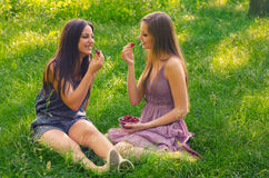 Girls eating strawberries in the nature Royalty Free Stock Images