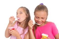Girls eating yogurt Stock Images