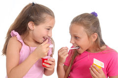 Girls eating yogurt Royalty Free Stock Photography