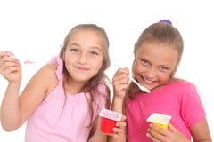Girls eating yogurt Royalty Free Stock Photos
