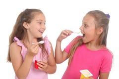 Girls eating yogurt. Two happy girls eating yogurt royalty free stock photo