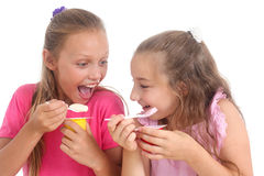 Girls eating yogurt Royalty Free Stock Photos