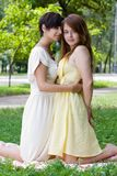 Girls embracing on the coverlet outdoors. Two girls chilling in the park on the coverlet upon green grass Royalty Free Stock Image