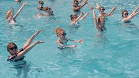 Girls are engaged in aqua aerobics. High-angle 4k shot: Young beautiful girls are engaged in aqua aerobics stock footage