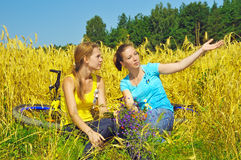 Girls enjoy the sight in golden field Stock Photos