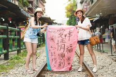 Girls enjoy Taiwan travel concept. Two girls showing their wishes on the sky lanterns in Chinese. Taiwan travel concept. Translation on sky lanterns text `hopes stock images