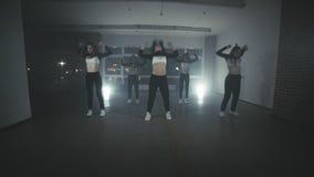 Girls enjoying funky hip hop moves in dark studio with smoke and lighting