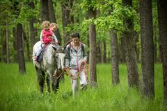 Girls enjoying horseback riding in the woods with mother, young pretty girls with blond curly hair on a horse, freedom. Joyful, outdoor, spring, healthy, happy stock photography
