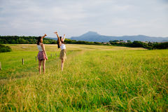 Girls enjoying nature. Happy female friends with arms raised enjoying nature and sun Stock Image