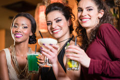 Girls enjoying nightlife in a club, drinking cocktails. Beautiful girls in nightlife drinking cocktails and saying Cheers Royalty Free Stock Photos