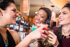 Girls enjoying nightlife in a club, drinking cocktails. Beautiful girls in nightlife drinking cocktails and saying Cheers Stock Image