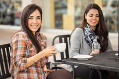 Girls enjoying some coffee outdoors. Portrait of a young women holding a cup of coffee while hanging out with her girlfriends at a cafe Royalty Free Stock Photos
