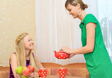 Girls Enjoying Tea. Two young women sitting at a table having tea Stock Photo