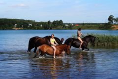 Girls and horses on the lake.