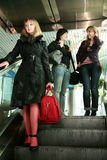 Girls on the escalator at the airport. People with bags on the escalator at the airport Royalty Free Stock Photography