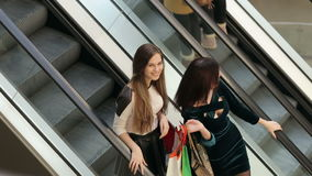 Girls on the escalator in the big shopping center. Two friends with purchases on the escalator in the big shopping center stock video