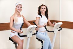 Girls on excercise bikes. Portrait of two girls exercising on excercise bikes in gym Royalty Free Stock Photos