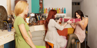 Girls exchanging gifts in colorful cafe Stock Photo