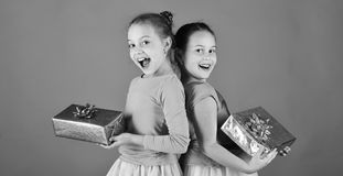 Girls with excited faces pose back to back with presents on green background. Children open gifts for Christmas. New Stock Photography