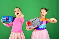 Girls with excited faces pose with presents on green background. New Year presents concept. Sisters with wrapped gift boxes for holiday. Children open gifts royalty free stock image